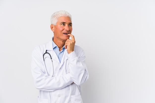 De rijpe kaukasische artsenmens ontspande het denken over iets bekijkend een exemplaarruimte.