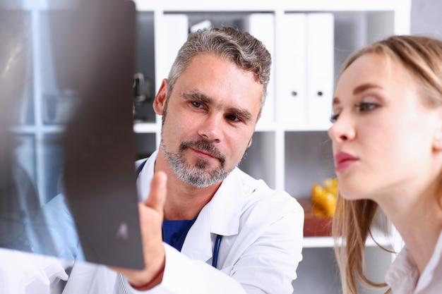 De rijpe mannelijke arts houdt in wapen en bekijkt xray fotografie