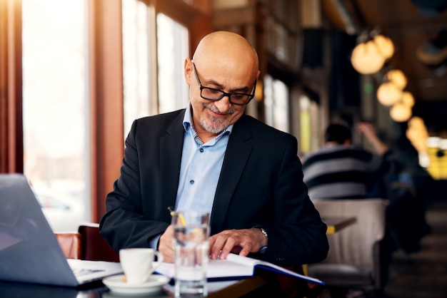 De rijpe professionele blije zakenman gebruikt laptop en drinkt koffie terwijl het maken van nota's in zijn notitieboekje in de koffiewinkel.