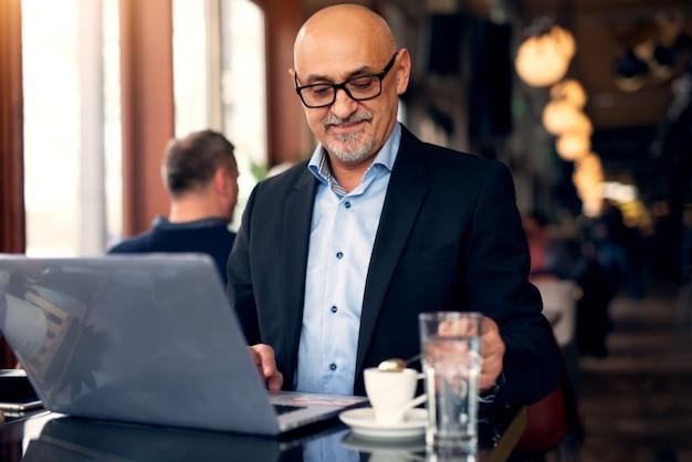 De rijpe professionele zakenman gebruikt laptop en drinkt koffie in de koffiewinkel