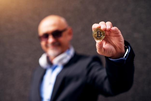 De rijpe vrolijke zakenman breidt wapen uit die een bitcoin toont aan de camera.