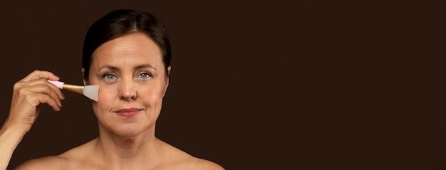 De rijpe vrouw die van smiley de borstel van het rozenkwartsgezicht met exemplaarruimte gebruikt