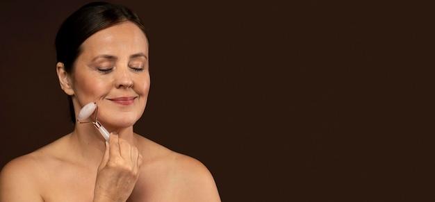 De rijpe vrouw die van smiley rozenkwartsroller op haar gezicht met exemplaarruimte gebruikt