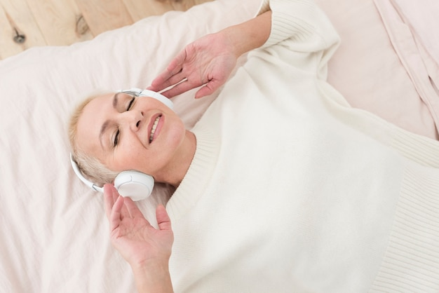 De rijpe vrouw die van smiley van muziek op hoofdtelefoons in bed geniet