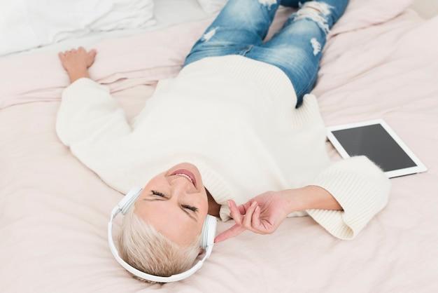 De rijpe vrouw van smiley in bed genieten die aan muziek in hoofdtelefoons luistert