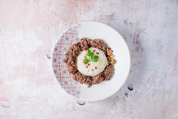 De rijst versiert met vleesballen in witte plaat.