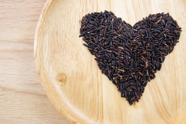 De rijstbes van het hart in houten kommen op houten achtergrond. concept