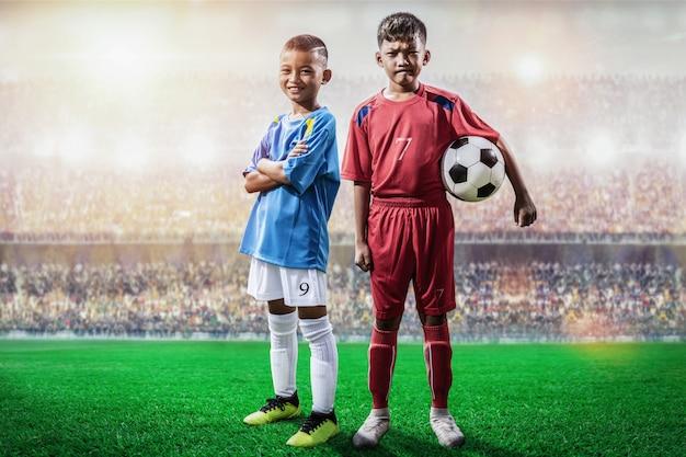De rivale speler van voetbaljonge geitjes in blauwe en rode jersey die en zich aan camera in het stadion bevinden stellen