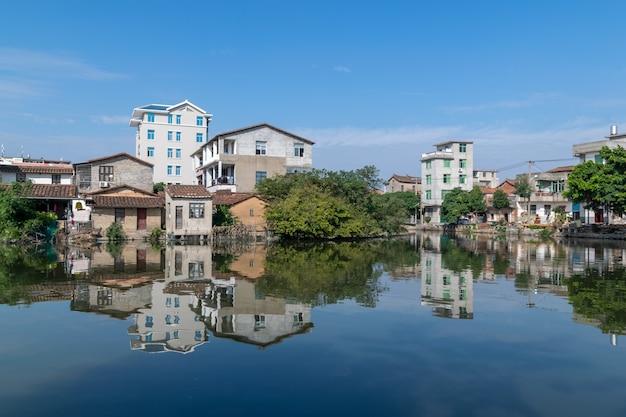 De rivier weerspiegelt het prachtige landschap aan beide kanten, met groene bomen en huizen.