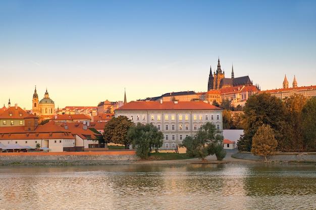 De rivieroever van ltava op zonsopgang, met st. vitus kathedraal en kasteel die erachter horizon vormen