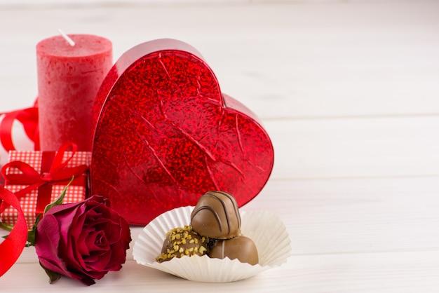 De rode achtergrond van de valentijnskaartendag met rode rozen en chocolade op een witte houten lijst.
