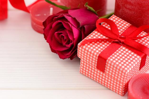 De rode achtergrond van de valentijnskaartendag met rode rozen op een witte houten lijst.