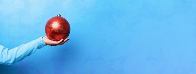 De rode bal van kerstmis overhandigt blauwe muur