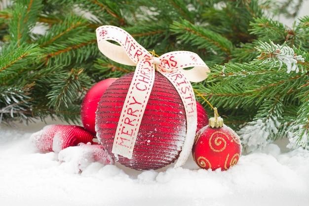 De rode ballen van de kerstmisbal met boog in sneeuw onder spar