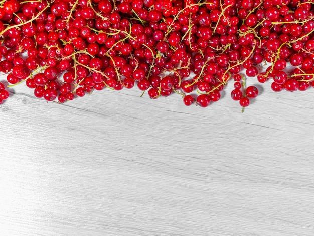 De rode bessen werden uit de struik geplukt en opgestapeld. half frame van rode aalbessen op wit bord.
