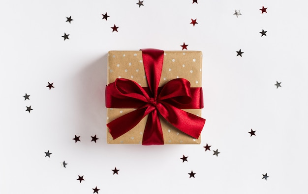 De rode boog van de de vakantiegiftdoos van kerstmis op verfraaide feestelijke lijst met fonkelingssterren