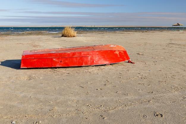 De rode boot van het metaal ligt op het zand door het meer