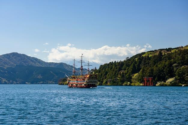 De rode cruise die van de piraattoerist door de rode toriipoort van het heiligdom van hakone bij ashi-meer, japan vaart