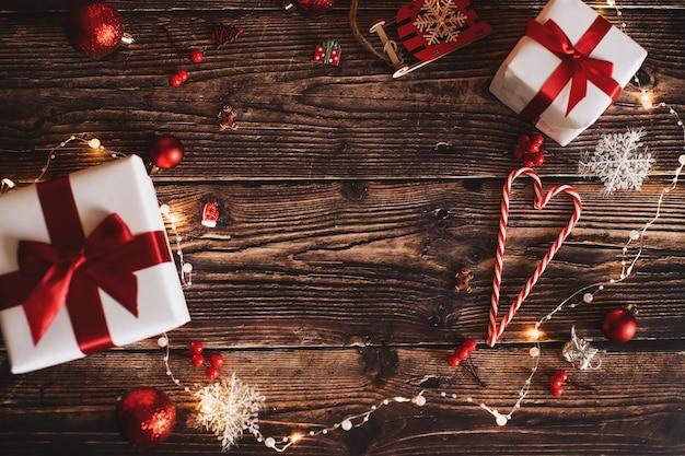 De rode de giftdoos en snuisterijen van kerstmis op achtergrond van defocused gouden lichten.