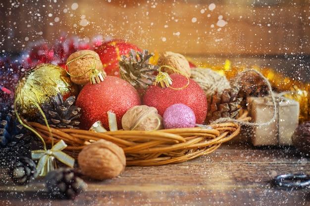 De rode en gele ballen van de kerstmissamenstelling, kegels, in een mand op houten