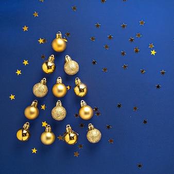 De rode gouden kleurrijke kerstboom gevormde samenstelling van decoratieballen op blauwe achtergrond