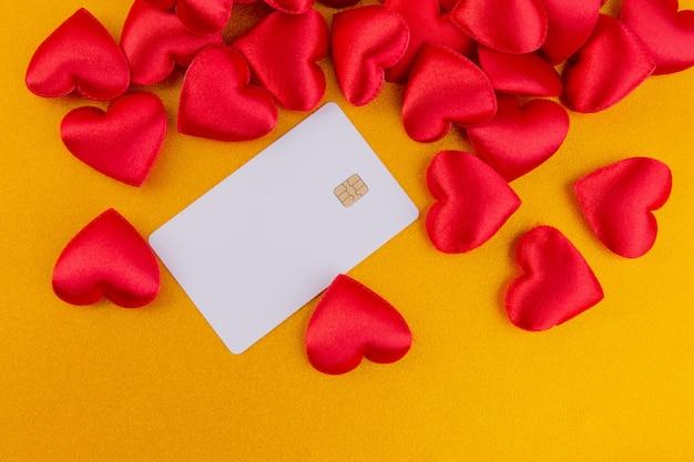 De rode harten met creditcard schitteren kleurengoud, de achtergrond van de valentijnskaartendag