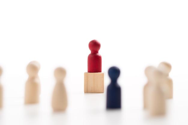 De rode houten figuur die op de doos staat, toont invloed en empowerment. concept van zakelijk leiderschap voor leidersteam, succesvolle competitiewinnaar en leider met invloed