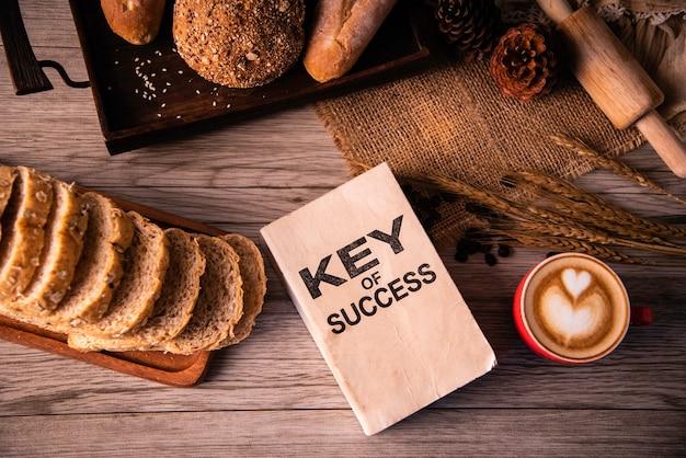 De rode koffiekop en de conceptenboeken voor succes leggen op de houten vloer - levensstijlconcept