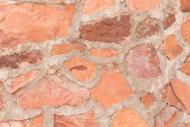 De rode openluchtachtergrond van de steenmuur en textuur van decoratieve leisteen