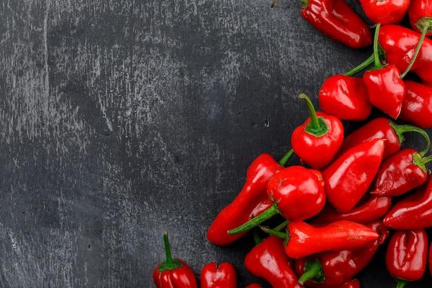 De rode paprika's op donkere grungemuur, leggen.