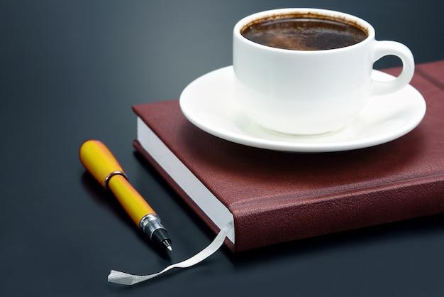 De rode pen is een schotel kopje zwarte koffie. kantoorartikelen