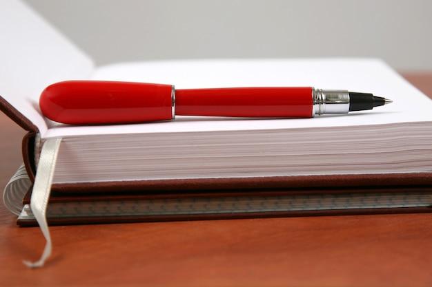 De rode pen liggend op een opengeslagen notitieboekje