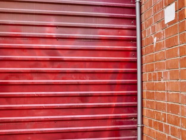 De rode poort van de metaalbakstenen muur op stadsachtergrond