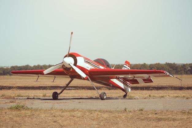De rode retro tribunes van het sportvliegtuig op gras tegen een blauwe hemel