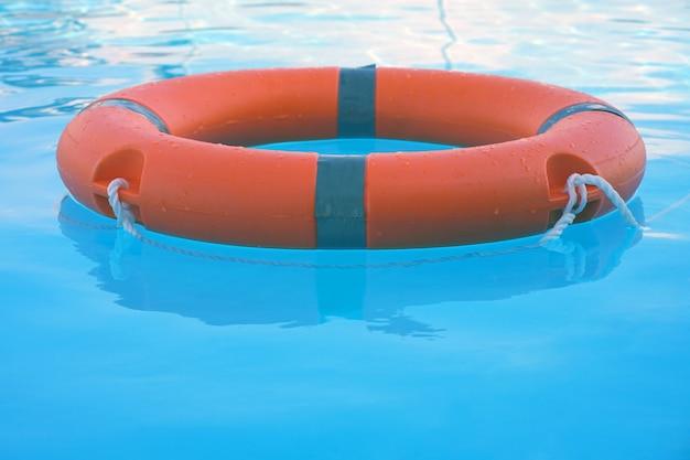 De rode ring van het reddingsboeipool drijft op blauw water. vaste ring drijvend bovenop zonnig blauw water. vaste voetring in zwembad