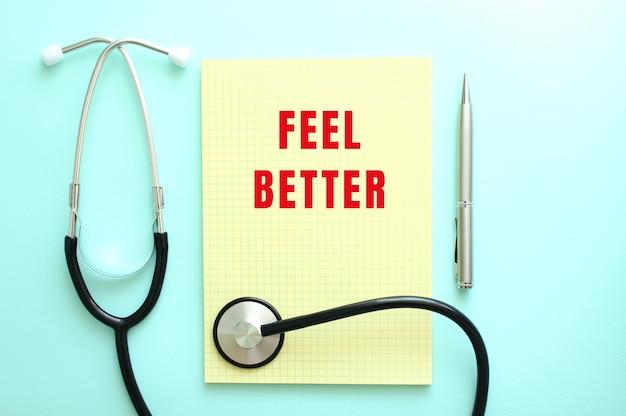 De rode tekst feel better is geschreven in een geel blok dat naast de stethoscoop op een blauwe achtergrond ligt.