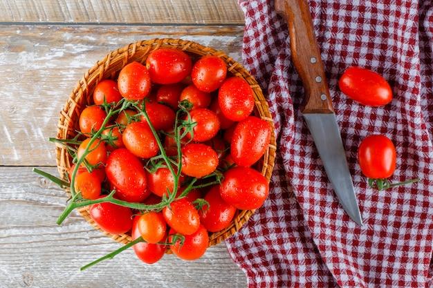 De rode tomaten in een rieten mand met messenvlakte leggen op houten en keukenhanddoek
