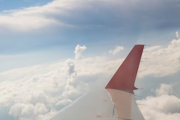 De rode vleugel van een vliegtuig in de blauwe lucht. wolken en lucht zichtbaar door de patrijspoort. concept - laten we vliegen om te rusten
