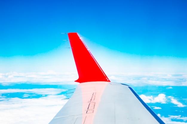 De rode vleugel van het vliegtuig op de achtergrond van een heldere blauwe lucht, het concept - we vliegen om te reizen