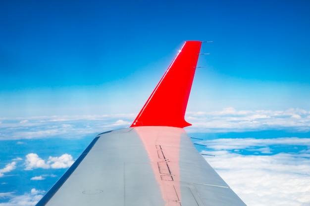 De rode vleugel van het vliegtuig op de achtergrond van een heldere blauwe lucht