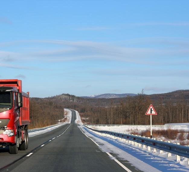 De rode vrachtwagen op een winter weg.