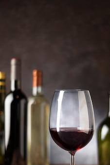 De rode wijnglas van de close-up met erachter flessen