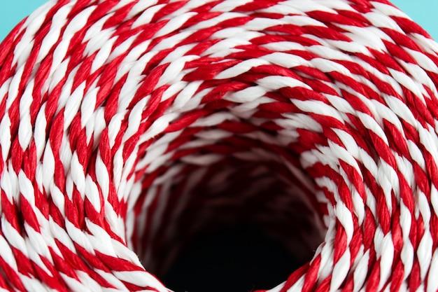 De rode witte kabel van verpakkingskerstmis op blauwe achtergrond