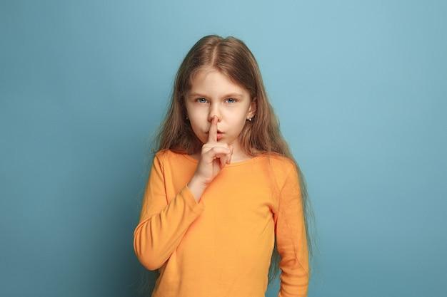 De roep om stilte. het tienermeisje dat om stilte vraagt in een blauwe studio