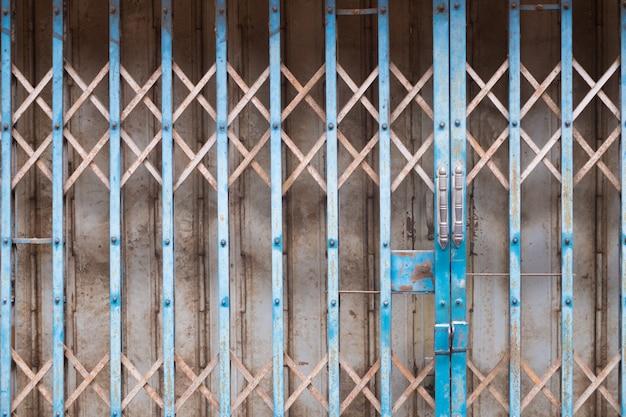 De roestige vintage stalen roldeur met slot.