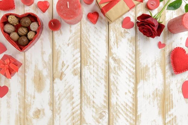 De romantische decoratie van de valentijnskaartendag met rozen en chocolade op een witte houten lijst. bovenaanzicht, kopie ruimte.