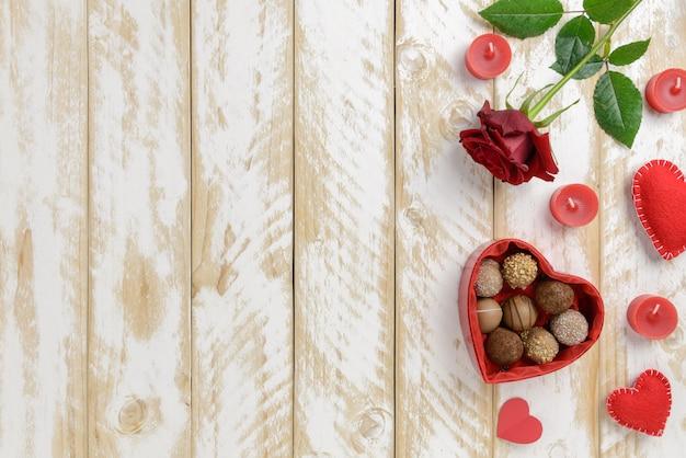 De romantische decoratie van de valentijnskaartendag met rozen en chocolade op een witte houten lijstachtergrond
