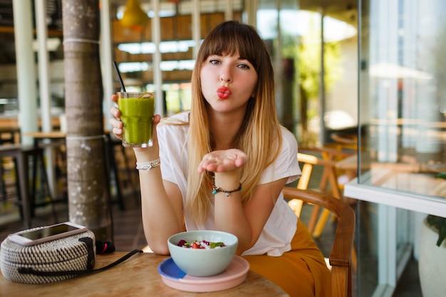 De romantische glimlachende vrouw verzendt kus en eet gezond veganistisch ontbijt.