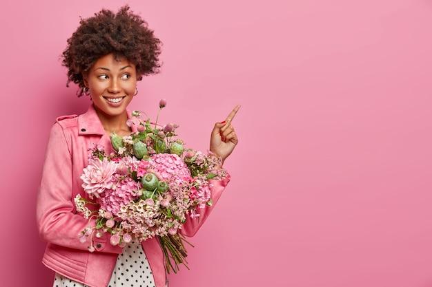 De romantische positieve jonge vrouw met afro-haar wijst wijsvinger aan kant, houdt mooi boeket van mengelingsbloemen