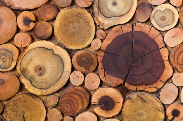 De ronde houten ongeverfde stevige natuurlijke ecologische zachte gekleurde bruine en gele stompenachtergrond, boom sneed secties verschillende grootte voor van de achtergrond stootkussenmat textuur.
